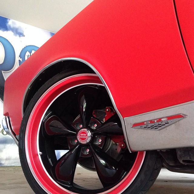Pontiac wrapped in Matte Red vinyl and Red Geranium Carbon Fiber vinyl on the wheel lip