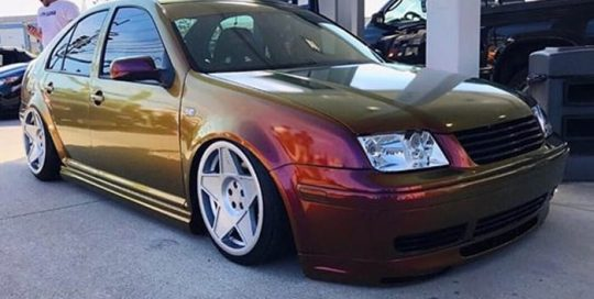 Volkswagen Jetta wrapped in Avery ColorFlow Gloss Rising Sun Red/Gold shade shifting vinyl