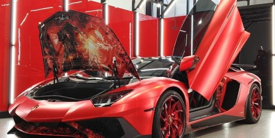 Lamborghini wrapped in Avery SW Red Chrome with 1370Z Luster overlaminate and custom printed 3M 1080 Satin Flip Ghost Pearl with 8518 Gloss overlaminate and accents in Orafol 970RA Black Honeycomb vinyl